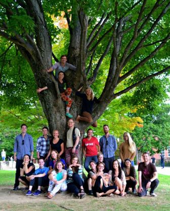 CMHC students in group ohoto, some in the limbs of a tree on campus